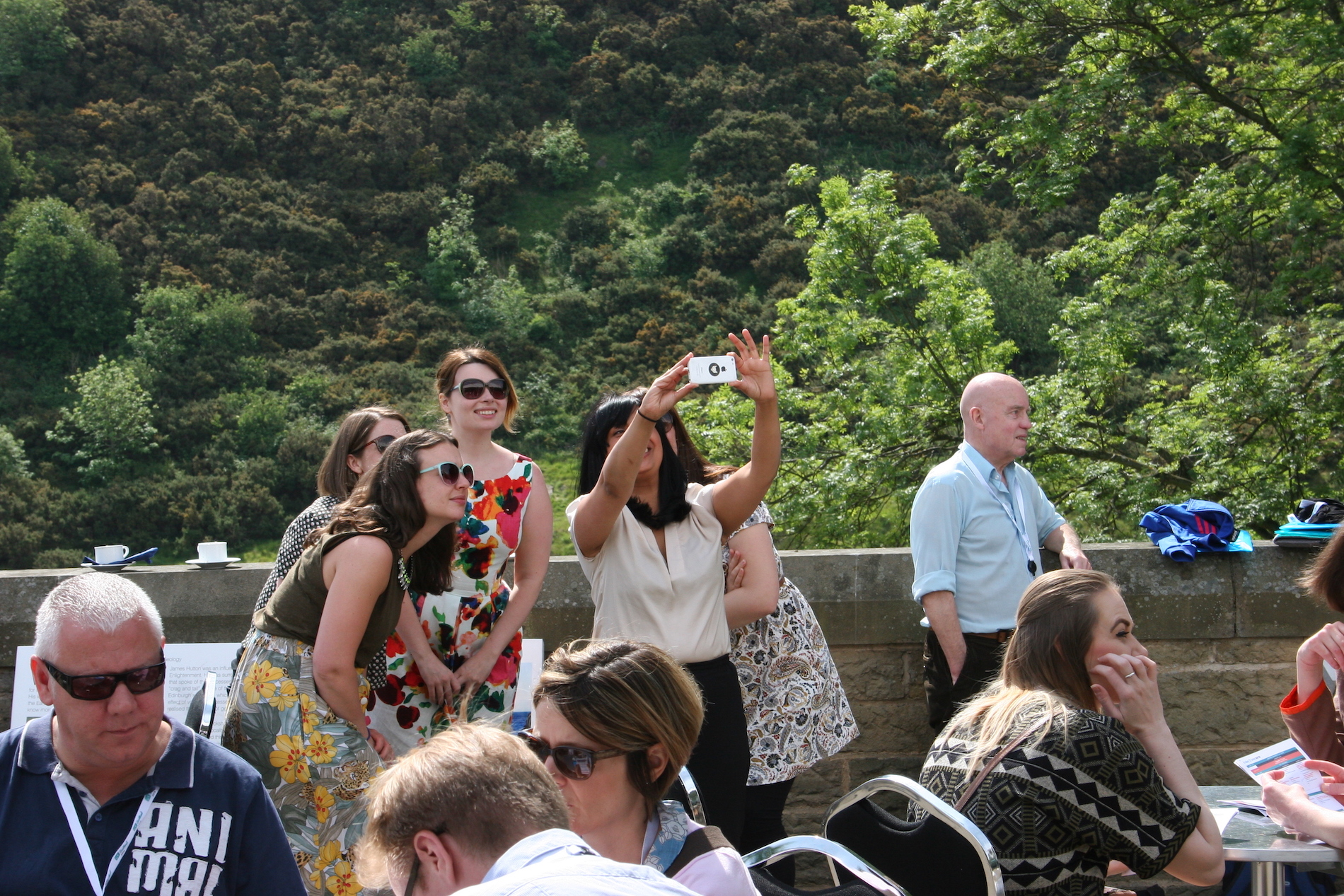 Participants taking a group selfie in the sunshine on the balcony at Dynamic Earth.