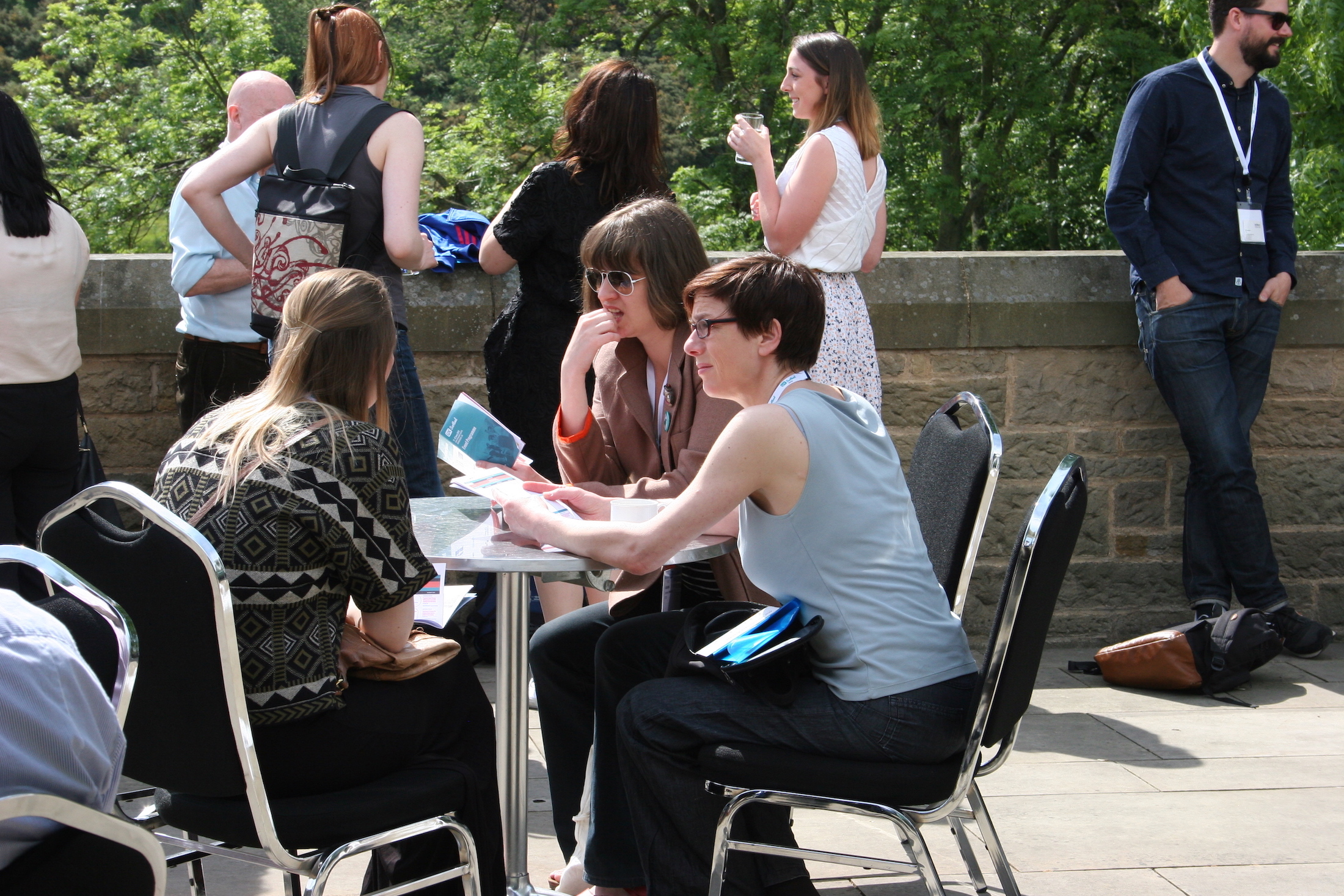 A group of participants sit around a small table, enjoying a refreshment break in the sun. They are looking at a participant booklet.